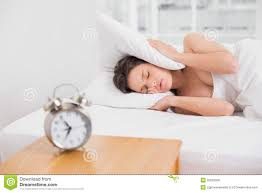 woman covering ears with pillow in bed and alarm clock on side
