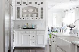 white kitchen cabinets with black knobs white mini subway tiles transitional kitchen rikki