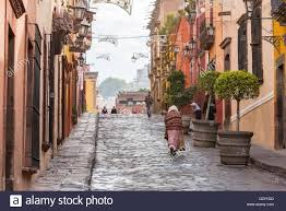 people walk past spanish colonial style homes along the