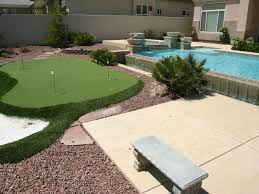 a putting green sits just beyond an infinity pool with a raised
