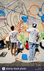 volunteer artists paint a wall mural as part of a community stock stock photo volunteer artists paint a wall mural as part of a community beautification project in santa ana ca