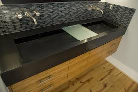 black tile trough bathroom sink with two faucets and brown wooden