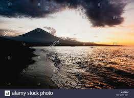 the volcanic black sand beach with the volcano gunung agung in the