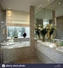 cream blind at window above bath in grey granite bathroom with