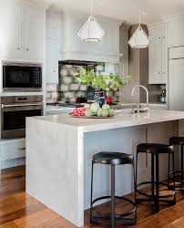 kitchen island with barstools backless black stools at honed white marble waterfall island