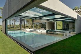 a pool with a glass bottom hovers over another at a house in the