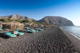 visit the black sand beach at perissa