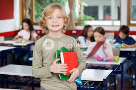 portrait of schoolboy holding books with classmates