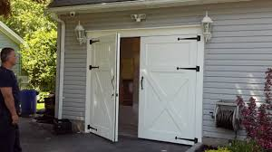 white barn style garage doors combine with gray wall paint color