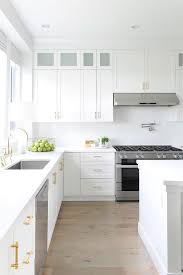 white shaker kitchen cabinets wood floors white and gold kitchen with light gray wash wood floors
