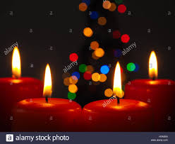 advent candles four burning advent candles with blurred lights background of a