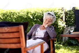 old woman sitting on chair looking at camera senior female