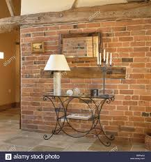 Exposed Brick Wall by Tall Cream Lamp On Metal Table In Front Of Exposed Brick Wall In