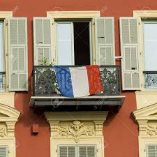 typical front of house in nice with french flag on a balcony stock