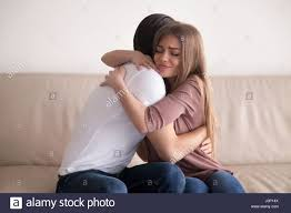 portrait of young couple hugging tight sitting on couch indoors