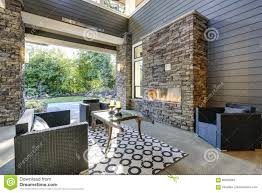 exterior covered patio with fireplace and furniture stock image