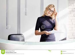 beautiful blonde friendly woman behind the reception desk