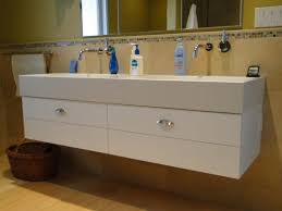 floating white concrete sink with white wooden vanity also steel