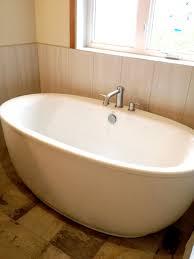White Rustic Laminate Flooring White Oval Standalone Bathtub On Black Wooden Laminate Flooring