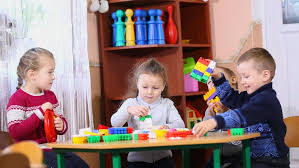 toddler boy enthusiastically plays metallophone in child room