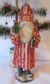 antique santa claus wearing a white striped coat antique