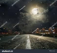 asphalt road leading into city night stock photo 150465248