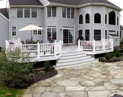 flagstone paver patio leads to low maintenance deck archadeck