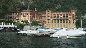 hotel on lake como near a docking area in italy stock video