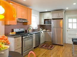 kitchen orange cupboards wtih modern oven and refrigerator white