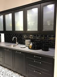 black kitchen cabinets with subway tiles and white frosted glass