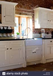 belfast sink below window in country kitchen with fitted cream