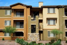 new 3 story condominium complex in gold and tan stucco with desert