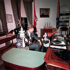 president kennedy laughs at the halloween costumes modeled by his