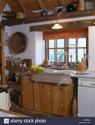 red blind on window above old earthenware sink in cottage kitchen