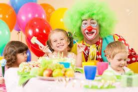 children celebrating birthday with clown stock photo