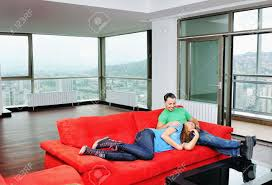Bright Red Sofa Happy Couple Relaxing On Red Sofa In Big Bright New Apartment