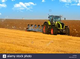modern farming with tractor in plowed field stock photo royalty
