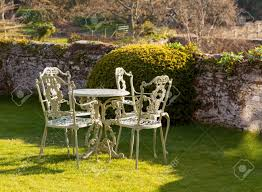 cast iron garden table and chairs on lawn by stone wall stock