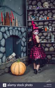in witch costume and makeup on her face standing in halloween