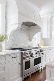 white curved kitchen hood white corbels white mosaic marble stove