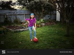 mixed race playing with soccer ball in backyard stock photo