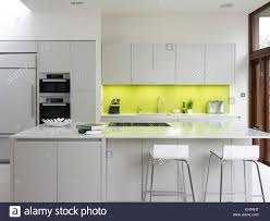 lime coloured backsplash in modern kitchen with inset oven and