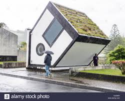 upside down house in the rain a man with an umbrella walks by the stock photo upside down house in the rain a man with an umbrella walks by the inverted house that s really an electrical transformer