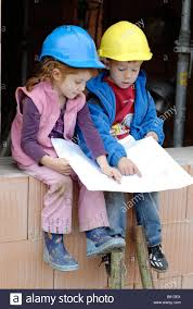 little house building plans two little children siblings wearing hard hats studying a