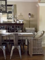 a mix of rustic metal chairs with wicker dining chairs pulled