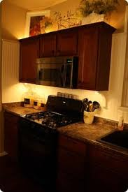 lights and greenery above the kitchen cabinets u0026 wreaths hanging
