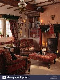 red armchair and upholstered stool in front of fireplace in cosy