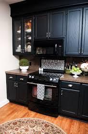 black cabinets with black appliances orange kitchen wall decoration and dark furniture in modern kitchen