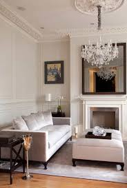 living room with a mirror over fireplace and crystal chandelier