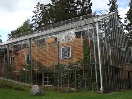 eco house couple surrounds eco home with greenhouse to keep it warm video